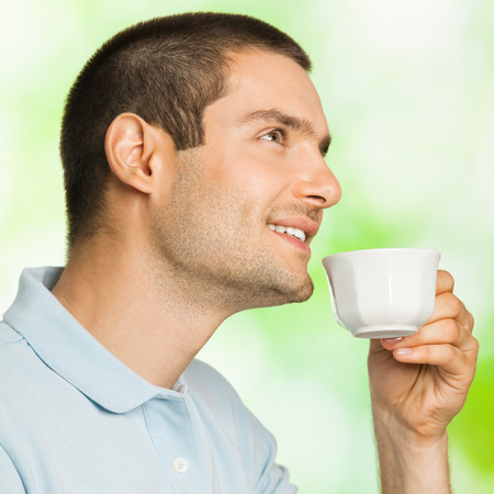 Portrait of young happy smiling man drinking coffee, outdoors photo