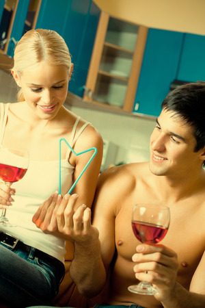 Couple celebrating with red wine and heart symbol made by combination of two cocktail tubules, at home photo