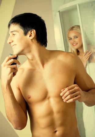 Shaving man and young woman at bathroom photo