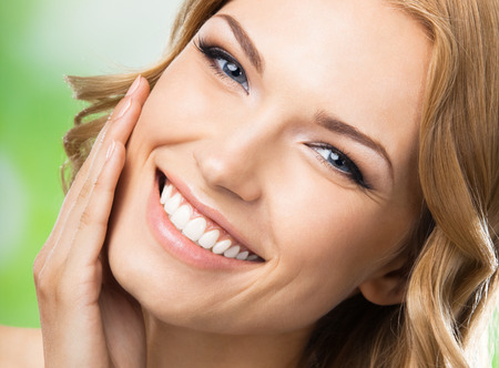 Portrait of happy smiling beautiful young woman touching skin or applying cream, outdoors photo
