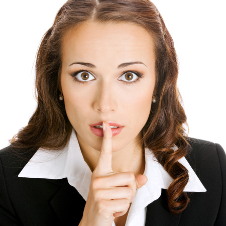 Portrait of young serious business woman keeping finger on her lips and asking to keep quiet, isolated over white background photo