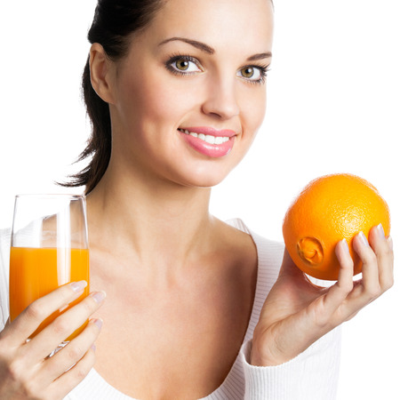 Portrait of happy smiling young woman with orange and glass of orange juice, isolated over white background photo