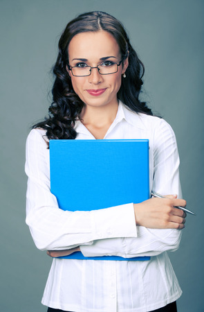Portrait of happy smiling business woman with blue folder, over gray background photo