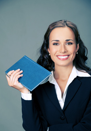 Portrait of happy smiling thinking business woman with blue notepad or organizer, over gray background photo