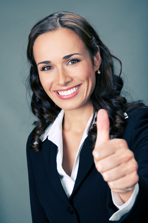 Happy smiling business woman showing thumbs up gesture, over grey background photo