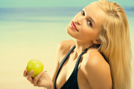 Portrait of young beautiful smiling woman with apple on sea beach  photo