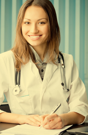 Portrait of happy writing young female doctor at office Stock Photo - 29750461