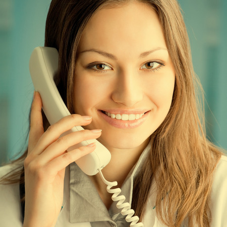 Portrait of happy smiling cheerful young female doctor on phone, at office Stock Photo - 29750462