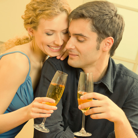 kiss couple: Portrait of cheerful smiling couple with champagne, indoors Stock Photo