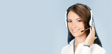 Portrait of happy smiling cheerful customer support phone operator in headset, over blue background
