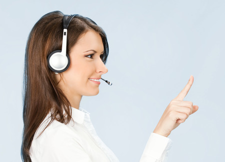 Portrait of happy smiling cheerful customer support phone operator in headset pointing at something, over blue background photo