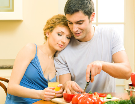 young couple smiling: Cheerful young cooking couple prepairing vegetarian salad at home