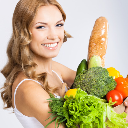 Portrait of happy smiling young beautiful woman with healthy vegetarian raw food, over gray background photo