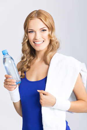 Portrait of cheerful young attractive blond woman in fitness wear with bottle of water and towel, over grey background photo