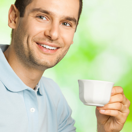 warm drink: Portrait of young happy smiling man drinking coffee, outdoor Stock Photo