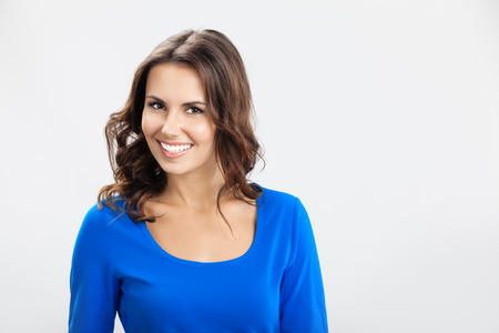 1 woman only: Portrait of young cheerful smiling woman, over grey  Stock Photo