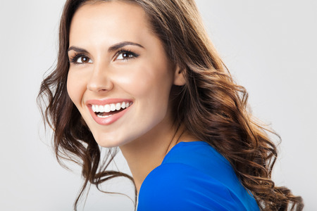 Portrait of young cheerful smiling woman, over grey  photo