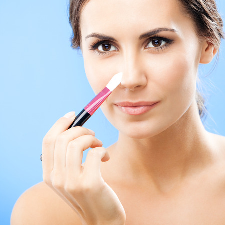Young woman with cosmetics brush, over blue photo