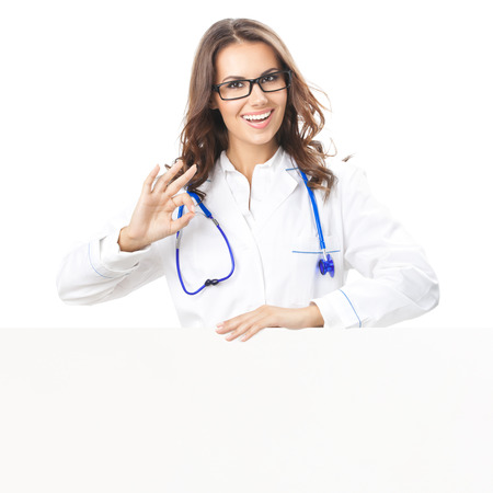 Portrait of happy smiling young female doctor showing blank signboard, with okay gesture, isolated over white  photo