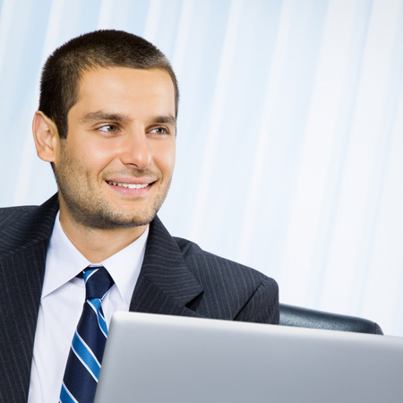 Successful happy smiling business man working with laptop at office photo