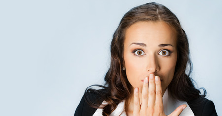 Portrait of surprised excited young business woman covering with hands her mouth, over blue background photo
