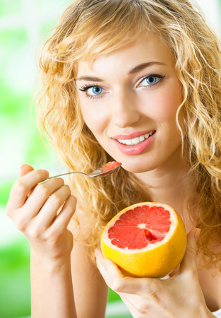 grapefruit: Portrait of young happy smiling woman eating grapefruit at home Stock Photo