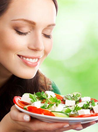 beautiful salad: Portrait of happy smiling woman with plate of salad, outdoor