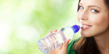 Woman drinking water from bottle, outdoor, with blank area for copyspace photo