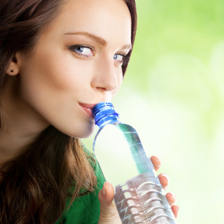 Woman drinking water from bottle, outdoor Stock Photo