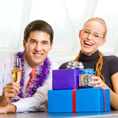 Two happy business people with champagne and gifts at celebration photo