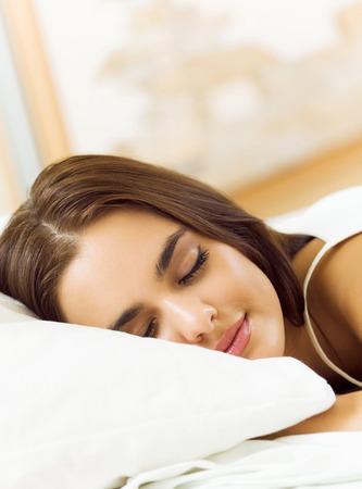 Young beautiful woman sleeping on bed photo
