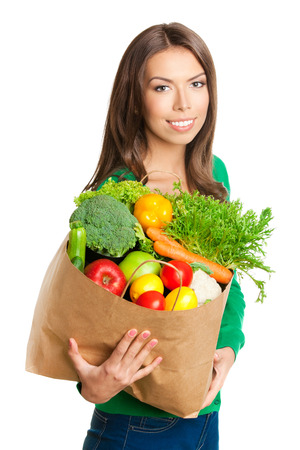 Portrait of happy smiling young beautiful woman with shopping bag of healthy vegetarian raw food, isolated over white background photo