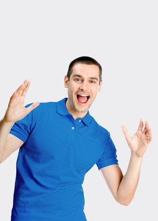 Expressive happy surprised man, against grey background photo