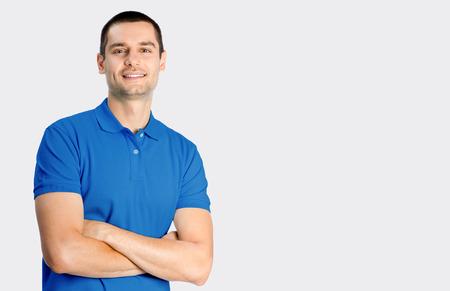 ropa casual: Retrato de hombre joven sonriendo feliz, contra el fondo gris