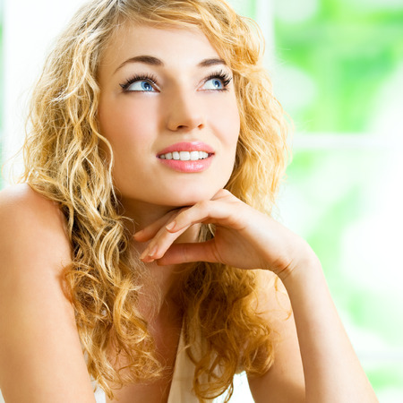Portrait of thinking young beautiful blond woman, at home photo