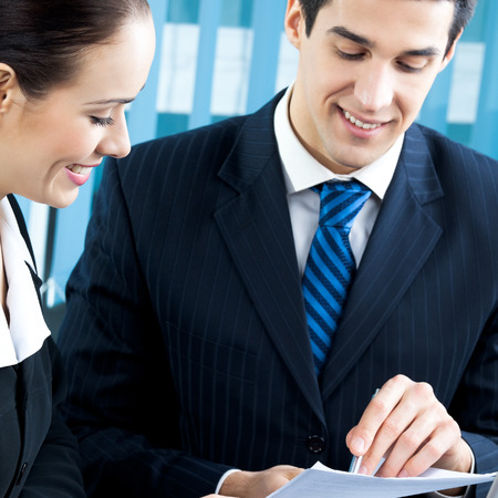 Two happy businesspeople working together at office. Focus on woman. photo