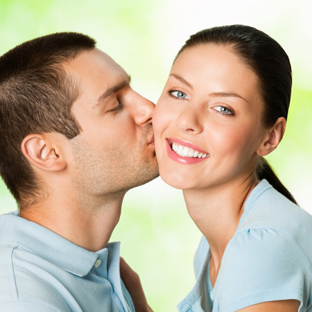 Portrait of beautiful young couple kissing, outdoor photo