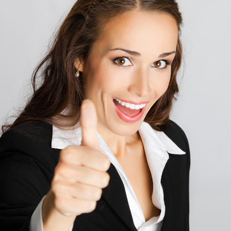 Happy smiling business woman showing thumbs up gesture, against grey background photo