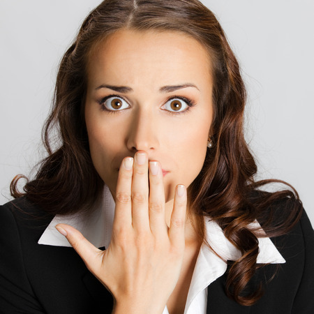 hand over: Portrait of surprised excited young business woman covering with hands her mouth, against grey background Stock Photo