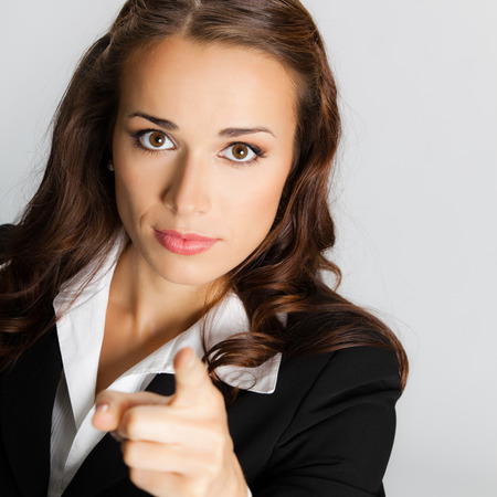 seriously: Portrait of young serious business woman pointing finger at viewer, against grey background Stock Photo