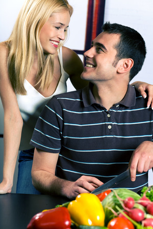 Young attractive happy smiling couple cooking at the kitchen photo