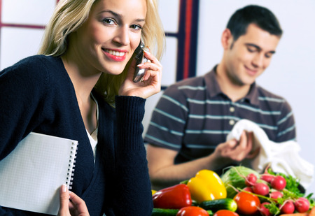 Young happy smiling attractive businesswoman on cellphone and cooking man at kitchen. Focus on woman. photo