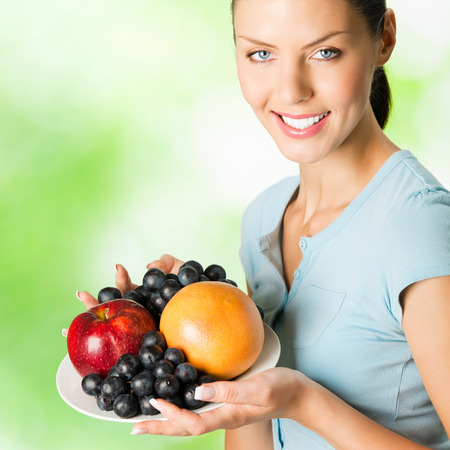 Young happy smiling woman with plate of fruits, outdoors photo
