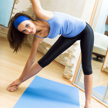 Young happy smiling woman exercising at home photo