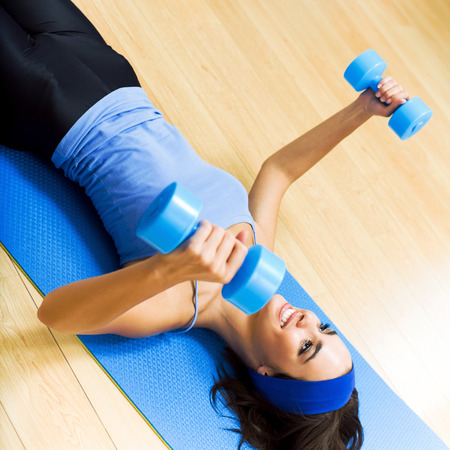 pumping: Young happy woman exercising with dumbbells at home Stock Photo