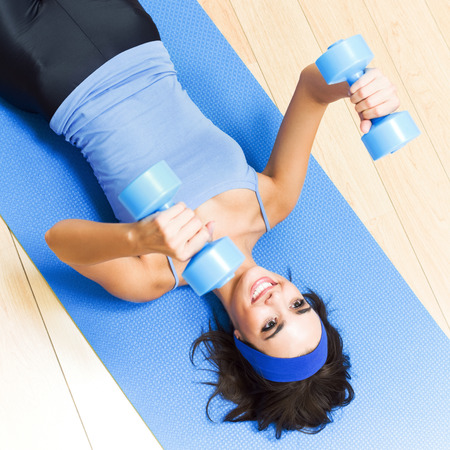 Young happy woman exercising with dumbbells at home photo