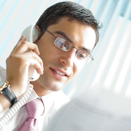 llamando: Empresario con teléfono y documentos en la Oficina