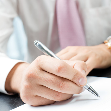 Closeup of writing businessman with document at office photo