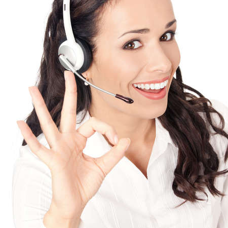 Portrait of happy smiling cheerful customer support phone operator in headset showing okay gesture, isolated on white background photo