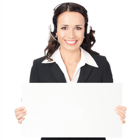 Happy smiling young customer support phone operator in headset showing blank signboard, isolated on white background photo